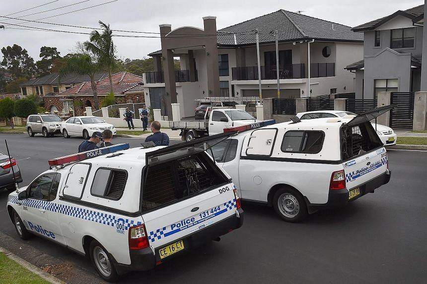 This man (above) and another three were detained during early morning raids in Sydney, Australia, yesterday. More than 200 police officers coordinated the raids on properties across the city (right) following a deadly attack last Friday.