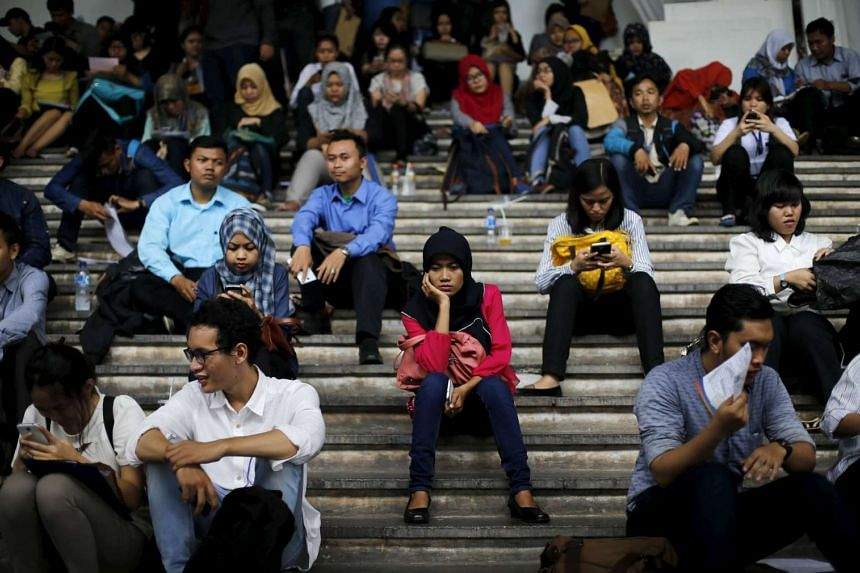 Job seekers are seen sitting on a flight of stairs at a job fair in Jakarta on Aug 12, 2015.