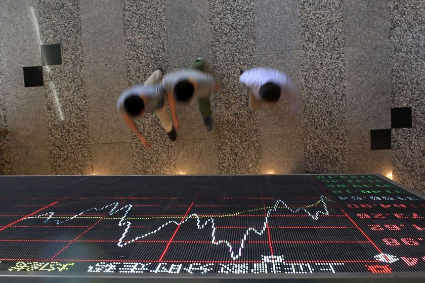 People walking under an electronic board showing stock information at the Shanghai Stock Exchange in China.