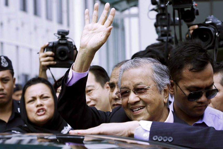 Former Malaysian prime minister Mahathir Mohamad waves to supporters as he arrives back at Subang airport, outside Kuala Lumpur, on Sept 9, 2015.