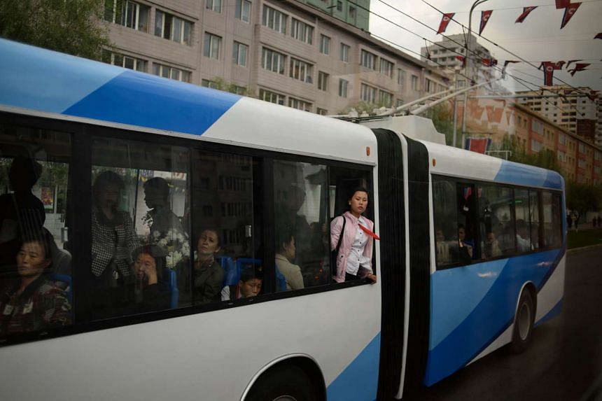 People look out from the window of a tram in Pyongyang on Oct 8, 2015.