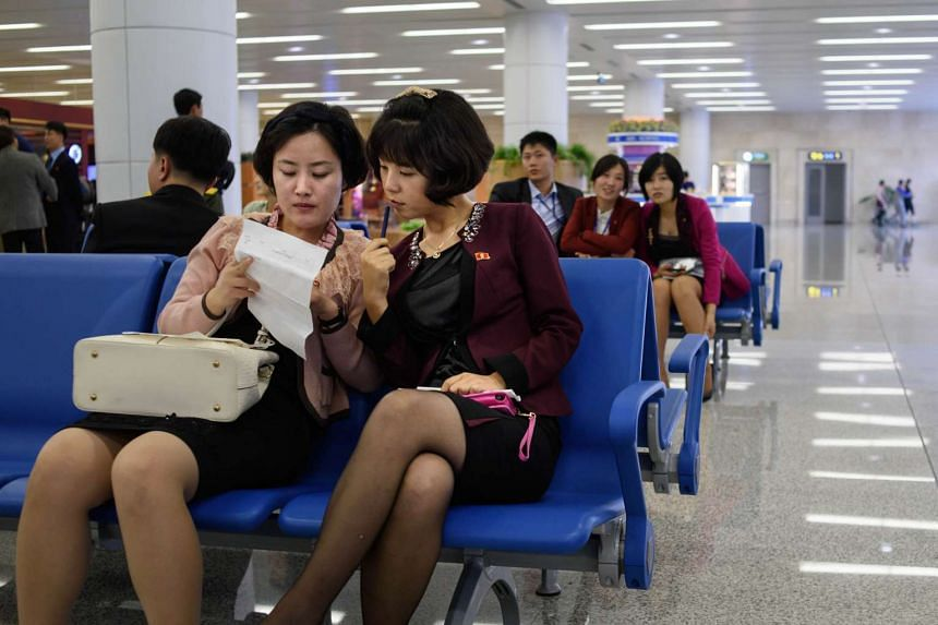 Two North Korean women sit in the arrivals hall at Pyongyang's International airport on Oct 8, 2015.