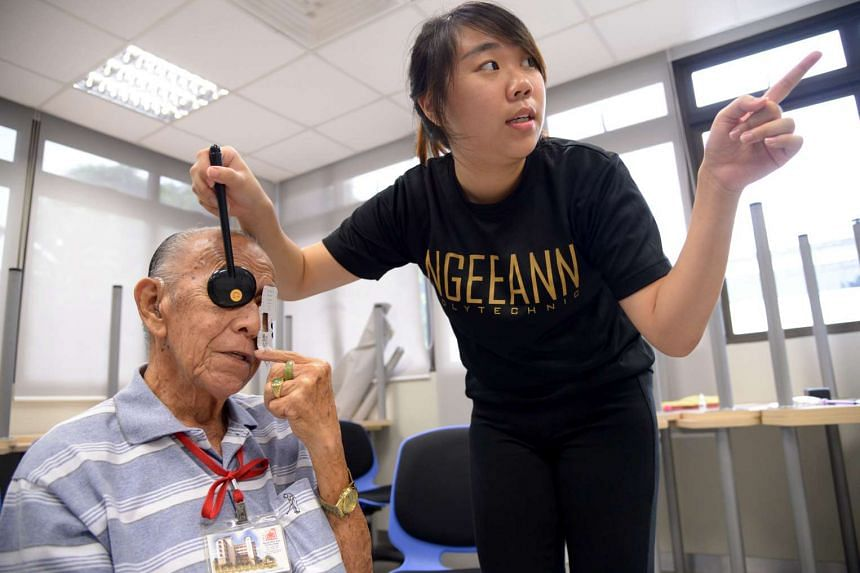 Mr Wee Chin Wei, (left), 84, from Kheng Chiu Loke Tin Kee Home, having his eyes checked by Ngee Ann Polytechnic student Brenda Ang, 19, a student pursuing her Diploma in Optomery, at Ngee Ann Polytechnic.