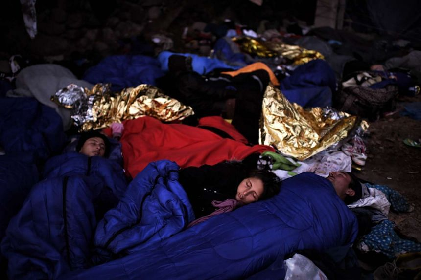 Refugees and migrants sleep on the street after arriving on the Greek island of Lesbos.