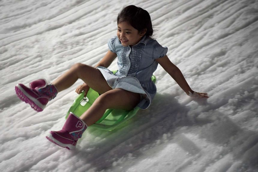 A girl keeps her balance while sledding at Snow Town in Bangkok, Thailand, on Aug 14, 2015.