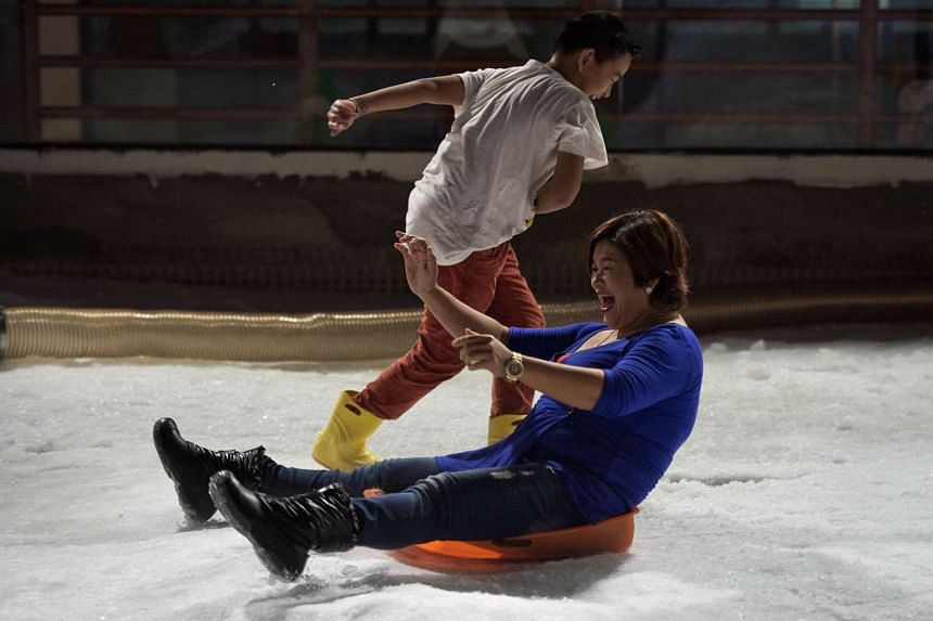 A woman laughs while sledding at Snow Town in Bangkok, Thailand, on Aug 14, 2015.