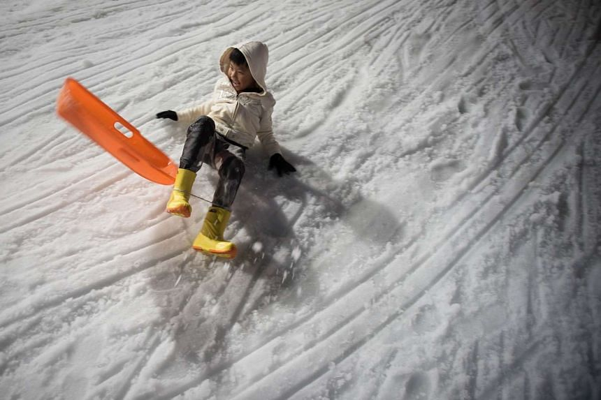 A boy laughs before he crashes while sledding at Snow Town in Bangkok, Thailand, on Aug 14, 2015.