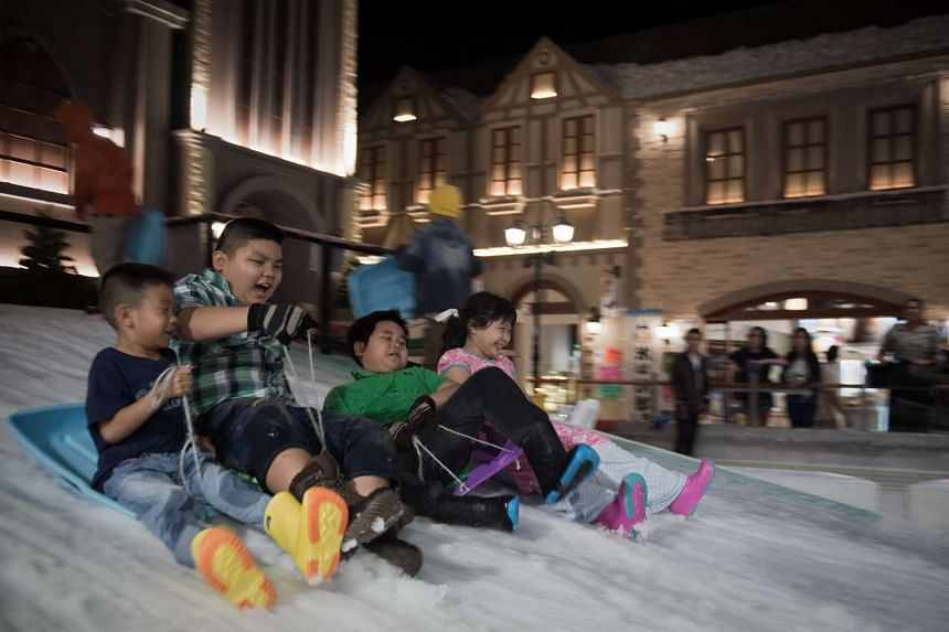 Children laugh and scream while sledding at Snow Town in Bangkok, Thailand, on Aug 14, 2015.