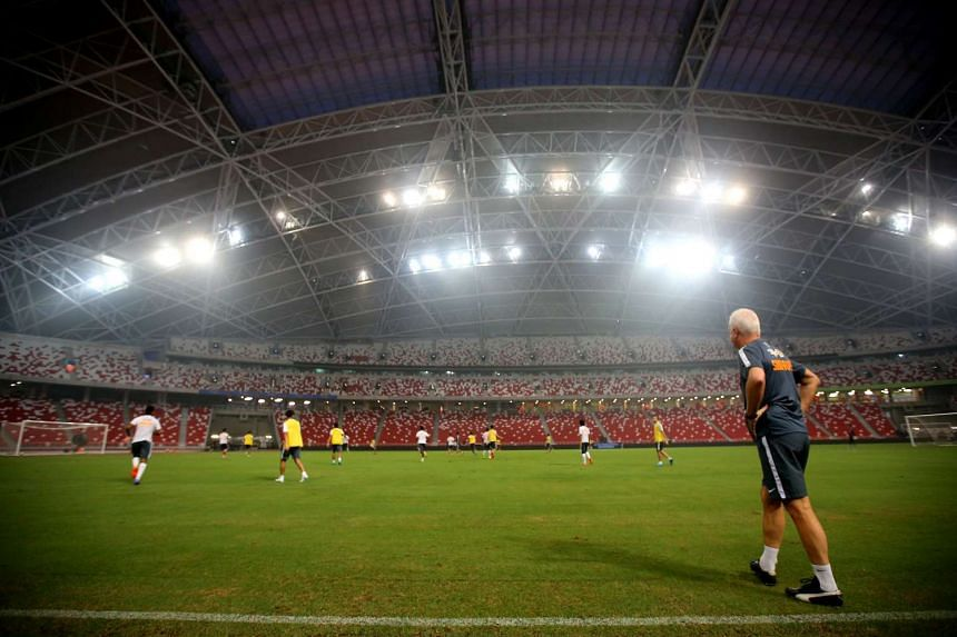 Bernd Stange (right) looking at his charges training ahead of World Cup Qualifier between Singapore and Afghanistan at National Stadium.