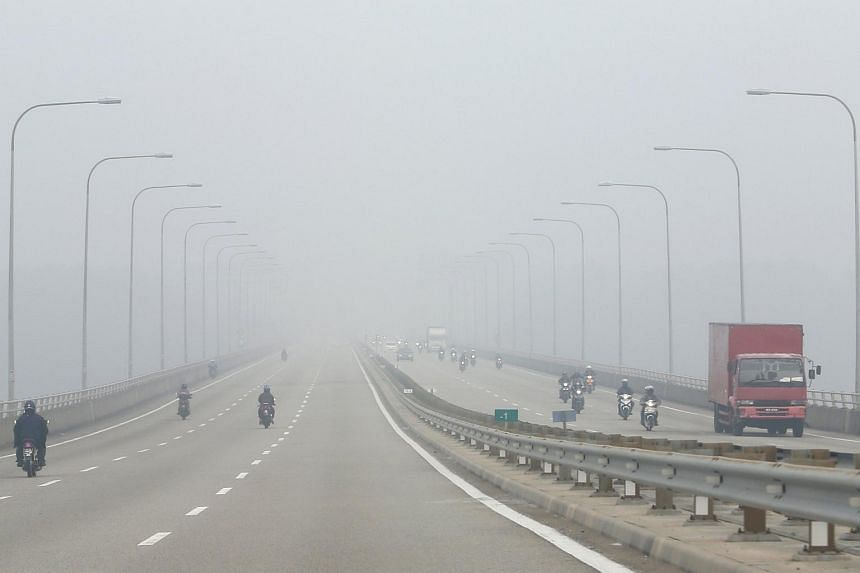 Motorists on a highway shrouded by haze in Johor on Oct 6.