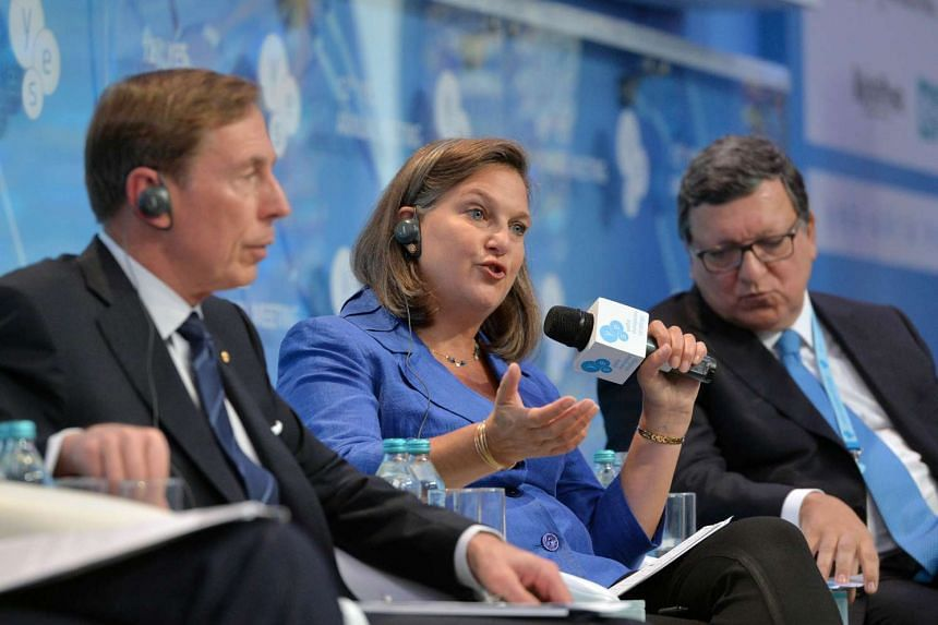 Victoria Nuland, US assistant secretary of state for European and Eurasian affairs, speaks next to former European Commission president Jose Manuel Barroso (R) and chairman of KKR Global Institute, former CIA director General David H. Petraeus, (L) d