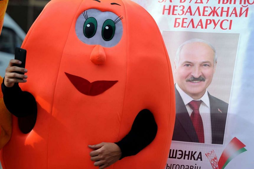 A man dressed as a pumpkin take a selfie next to a poster bearing the image of Belarus' President Alexander Lukashenko as his supporters collect signatures to register him as a candidate for the October 11 presidential elections, in Minsk on Sept 19,
