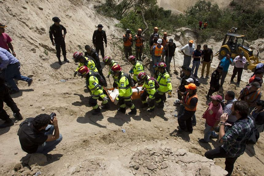 Firefighters rescue Rony Pu alive after a landslide in El Cambray II village, Santa Catarina Pinula municipality, Guatemala, on Oct 2, 2015