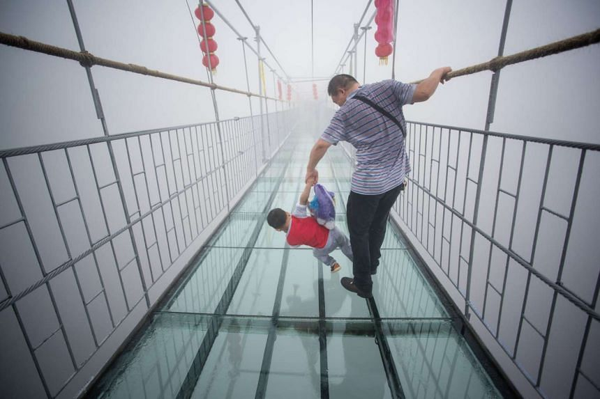 A Chinese tourist holds onto his son as they walk across a glass-bottomed suspension bridge in the Shinuizhai mountains in Pingjang county, Hunan province some 150km from Changsha on Oct 7, 2015. The bridge, originally a wooden walkway spanning some