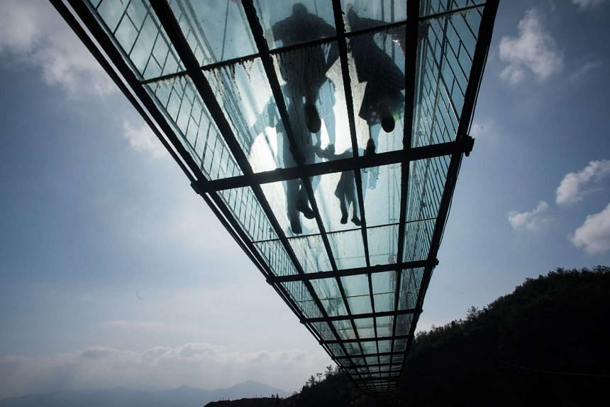 Chinese tourists walk across a glass-bottomed suspension bridge in the Shinuizhai mountains in Pingjang county, Hunan province some 150 kilometers from Changsha on Oct 8, 2015. The bridge, originally a wooden walkway spanning some 300m across the 180