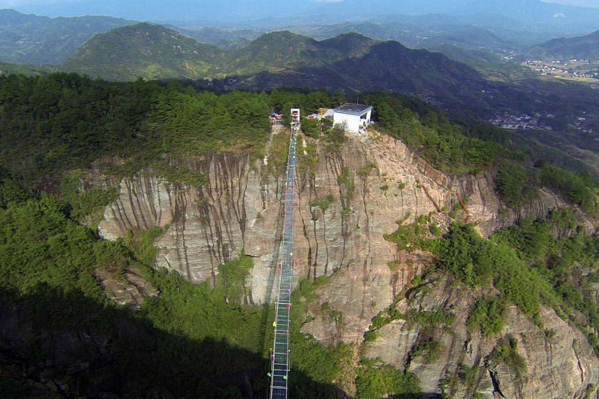 A view shows the glass-bottomed suspension bridge in the Shinuizhai mountains in Pingjang county, Hunan province some 150 kilometers from Changsha on Oct 8, 2015. The bridge, originally a wooden walkway spanning some 300 meters across the 180m-deep