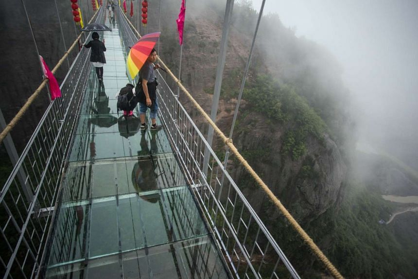 Chinese tourists walk across a glass-bottomed suspension bridge in the Shinuizhai mountains in Pingjang county, Hunan province some 150 kilometers from Changsha on Oct 7, 2015. The bridge, originally a wooden walkway spanning some 300 meters across t