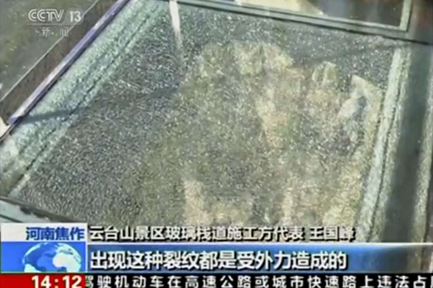 A view of cracked glass on a panel of the glass walkway at Yuntai Mountain Park in China's northern Henan province is seen in this still image obtained from video on Oct 7, 2015. An official at the park said on Wednesday that the glass walkway, which