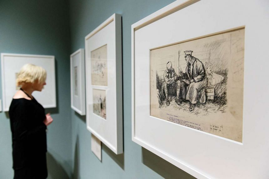 """A gallery assistant poses in front of war-time drawings by British illustrator E H Shepard at a press preview of """"EH Shepard: An Illustrator's War"""" at the House of Illustration in north London on Oct 8, 2015."""