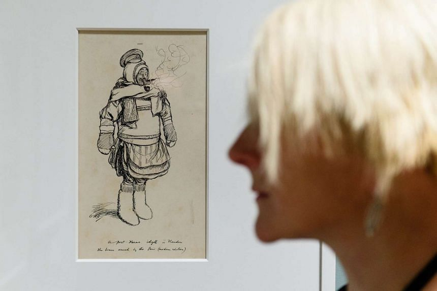 """A gallery assistant poses in front of a drawing by British illustrator E H Shepard entitled """"Gallant attempt by a member of the British Expeditionary Force to do justice to all his New Years' gifts"""" at a press preview of """"EH Shepard: An Illustrator's"""