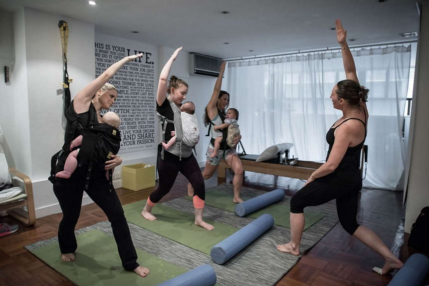 Mothers with their babies attending an exercise class dubbed 'Mumba', a new twist on the baby-wearing trend gripping mothers in Hong Kong.