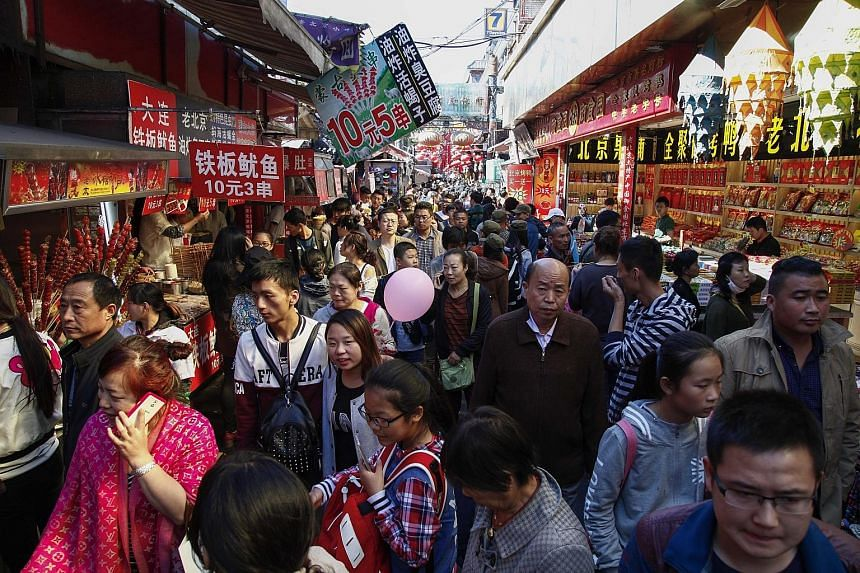 Tourists thronging a busy food street in the Wangfujing shopping and tourist district in Beijing on Oct 1. Despite a rocky economy, many cities and provinces across China reported higher tourist numbers and receipts.