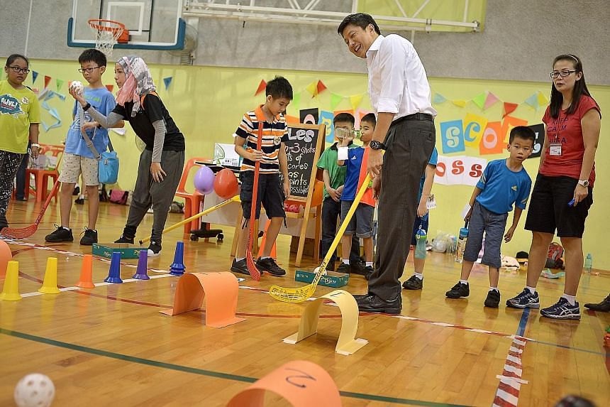 Acting Minister for Education Ng Chee Meng trying out Score! Score!, a game organised by pupils from Frontier Primary's Red Cross CCA, at the school's Children's Day carnival yesterday.