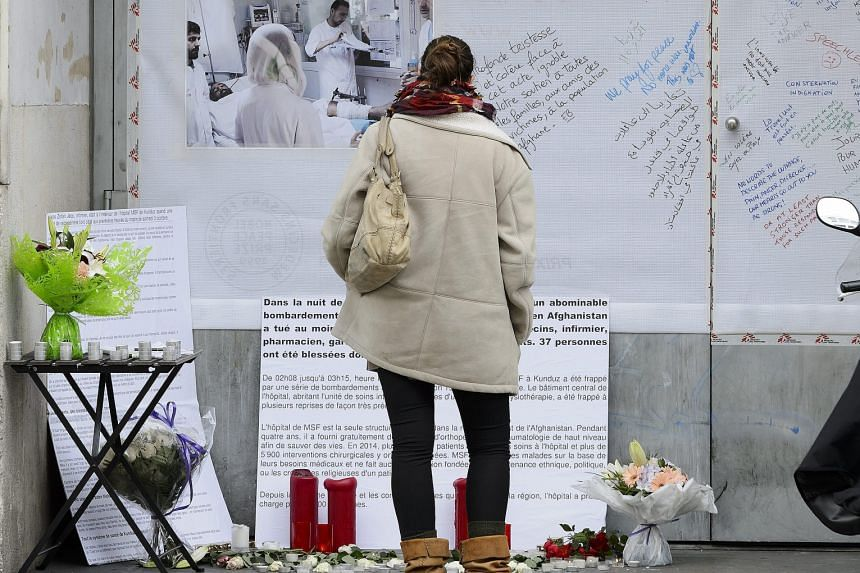 A woman reading messages left outside the headquarters of Doctors Without Borders in Geneva, Switzerland, on Wednesday in the wake of the US bombing of the group's field hospital in the Afghan city of Kunduz last Saturday.