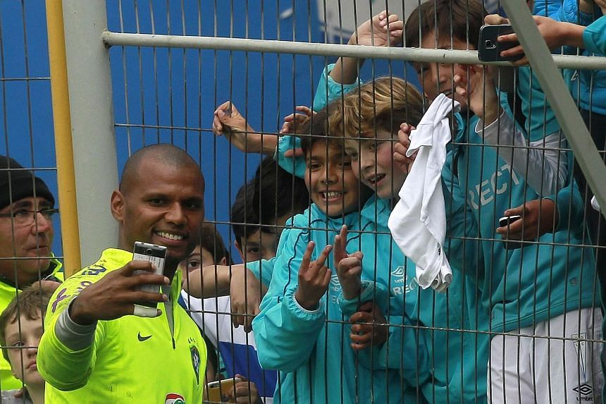 "Brazil goalkeeper Jefferson takes a ""wefie"" with fans as the Selecao trained in Santiago before their crunch tie against Chile."