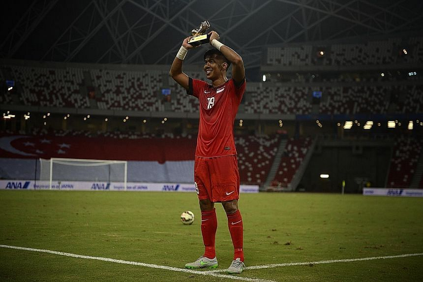 Above: Khairul Amri scoring the lone goal with a header from a corner kick. Left: Singapore's fans celebrate in a relatively empty stadium, with only 7,128 turning up. Right: Amri with the trophy awarded for joining the century club in terms of inter