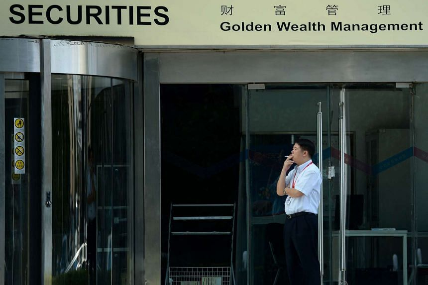 A man smoking at the entrance to a securities firm in Beijing.