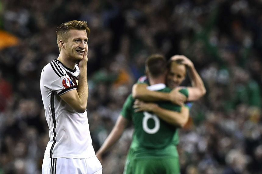 Germany's midfielder Marco Reus (left) reacts after losing, as Republic of Ireland players celebrate.