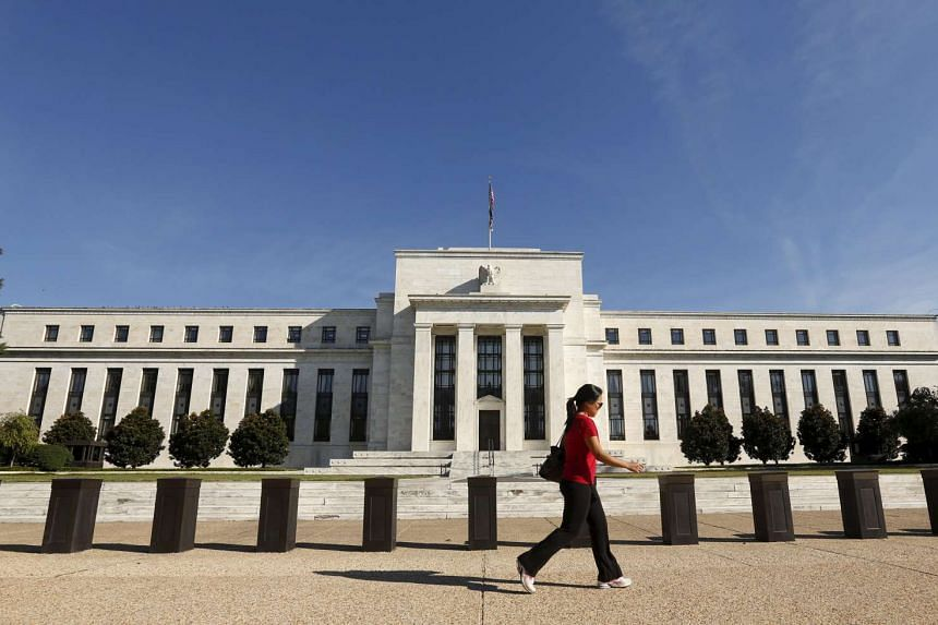 A woman walks past the Federal Reserve headquarters in Washington Sept 16, 2015.
