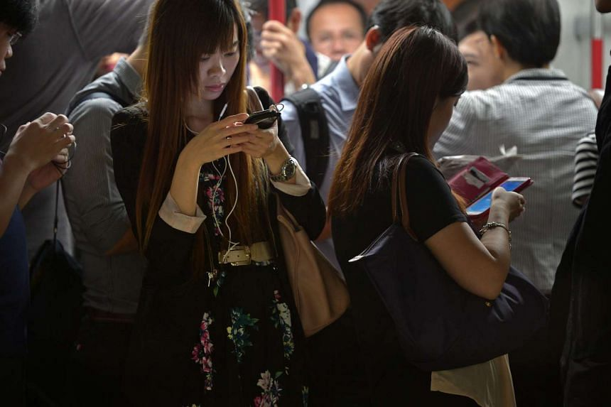 Commuters using their mobile phones in a train in Hong Kong.