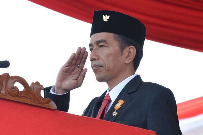 Indonesia's President Joko Widodo saluting during the 70th anniversary celebrations of Indonesia's armed forces at the naval port in Cilegon, West Java province.