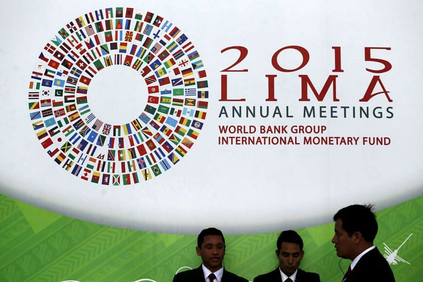 People stand near a welcome sign to the 2015 IMF/World Bank annual meetings in Lima.