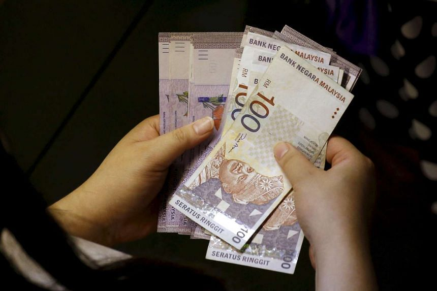 A customer counting ringgit notes outside a money changer in Singapore.