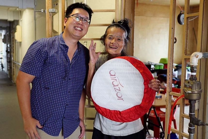 Madam Huang, a resident of Block 8, North Bridge Road, holding an air filter she received from Mr Wally Tham.