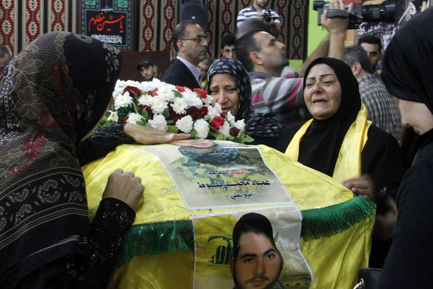 Women mourn next to the coffin of one of the two members of Lebanon's Shiite Hezbollah movement who were killed in combat alongside Syrian government forces fighting against Islamic State group jihadists in Syria's Qalamun region boarding Lebanon, du