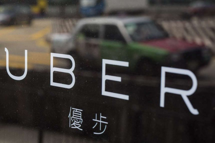 A taxi is reflected in a window at the office of taxi-hailing service Uber Inc in Hong Kong, China.