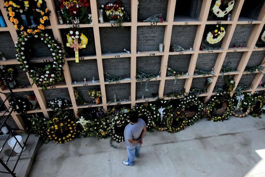 A man watches some of the tombs of some victims of the landslide in settlement El Cambray II, which has left for the moment 215 deads, in Santa Catarina Pinula, Guatemala, on Oct 8, 2015.