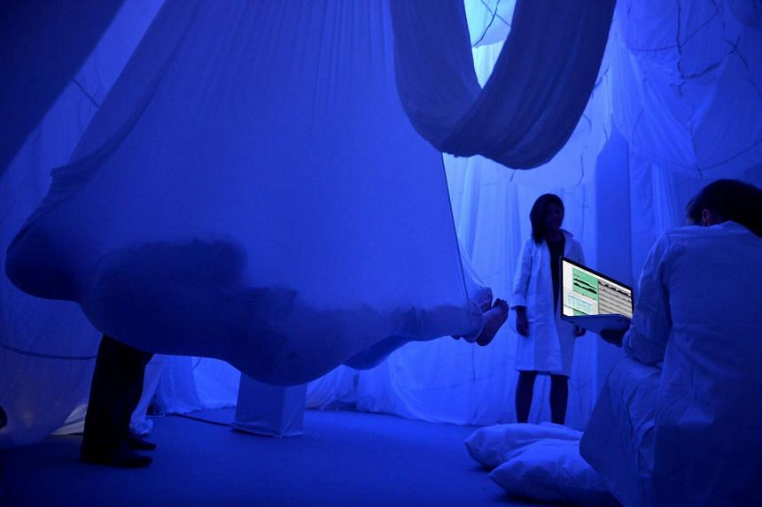 """Lab asistants"" helping members of the media get into their hammocks at the The Chronarium, a public sleep lab designed by British artist Rachel Wingfield during a media preview of the Festival of Tech at The Cathay."