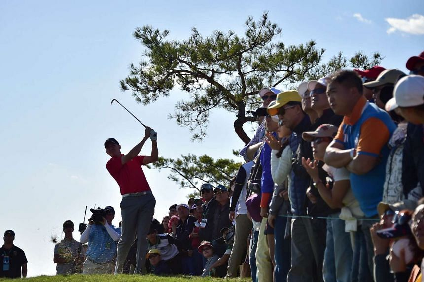 Jimmy Walker of the US (left) hitting an approach shot on the 18th hole during the second round four-ball matches at the 2015 Presidents Cup in Incheon, Seoul, on Oct 9, 2015.