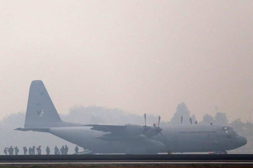 Malaysian aircrew members diesmbark from a C-130 military aircraft as they arrive at Sultan Mahmud Badaruddin airport in Palembang, South Sumatra, Indonesia, Oct 9.