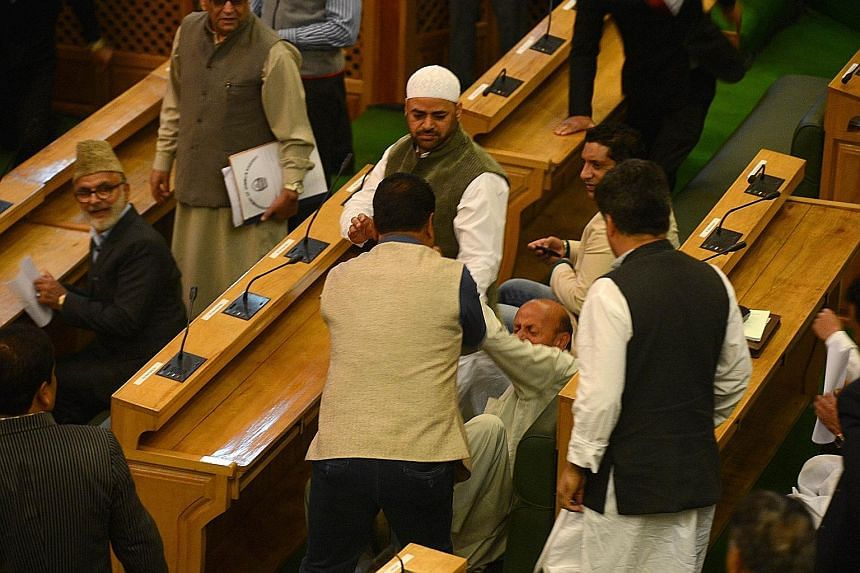 Opposition Muslim member Abdul Rashid (centre) falls after being punched and shoved by BJP legislators in the Jammu and Kashmir state assembly on Thursday. He had served beef at a party in protest over a ban on killing and eating cows in India's only