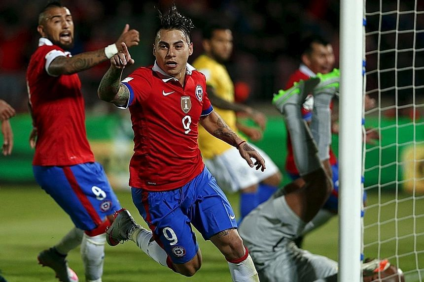 Above: The injury suffered by Sergio Aguero, who scored five goals for Manchester City against Newcastle last Saturday, means that the striker will not play in Argentina's match against Paraguay on Tuesday. Left: Chile's Eduardo Vargas (front), who s