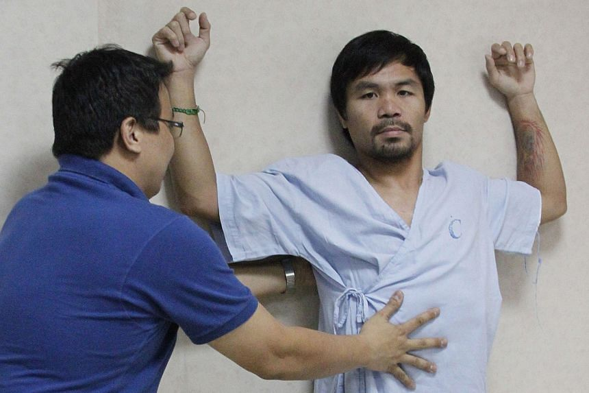 Manny Pacquiao being coached by a Philippine doctor to do some exercise two weeks ago to rehabilitate his right shoulder rotator cuff, which he injured while training for May's mega-bout with the American Floyd Mayweather. The boxer intends to have o