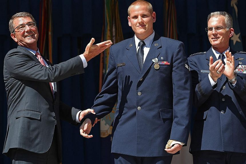 Mr Spencer Stone being congratulated on his heroic act by US Defence Secretary Ashton Carter (left) and vice-chairman of the Joint Chiefs of Staff, General Paul Selva, at an awards ceremony at the Pentagon last month.
