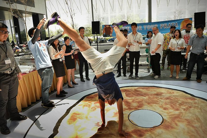 From K-pop to hip hop, workers in the Central Business District showed their dance moves for free roti prata on Thursday. The Dance For Your Prata lunchtime event took place at The Cube, a plaza linking the two towers of Asia Square in Marina Bay. It