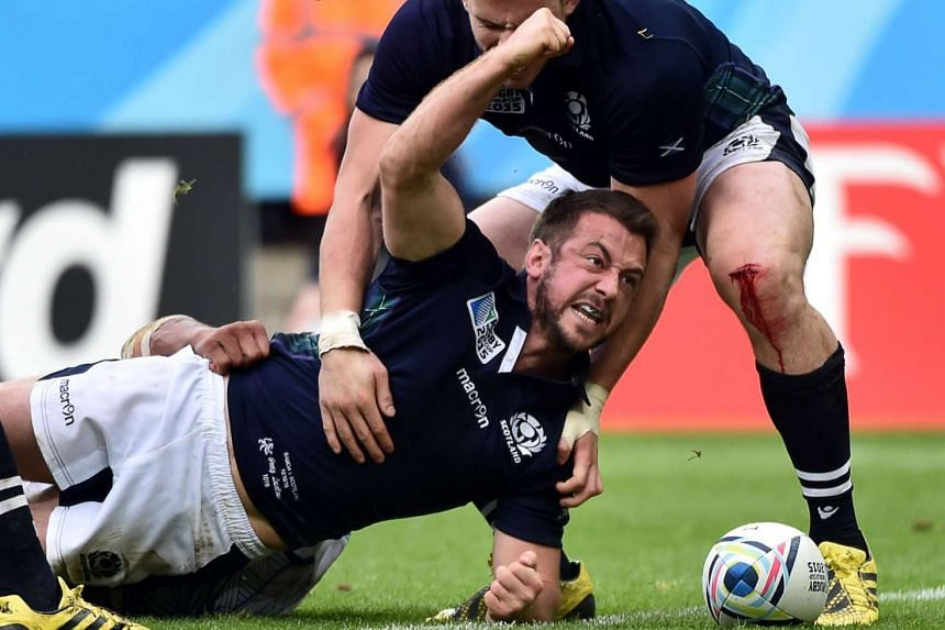 Scotland's scrum half and captain Greig Laidlaw celebrates scoring his team's third try.